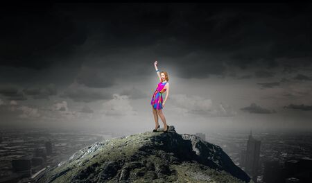 charming girl: Young girl in multicolored bright dress on rock top