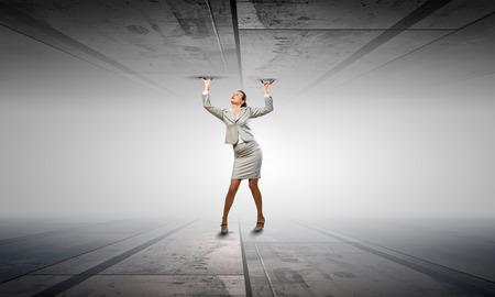claustrophobia: Businesswoman under pressure between two stone walls