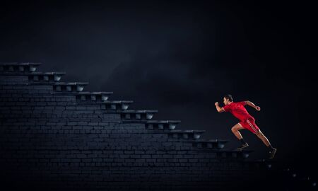 male athlete: Athlete man in red sport wear running up staircase