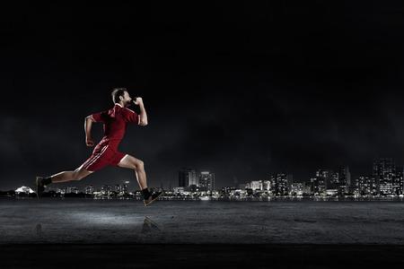 atleta corriendo: Hombre corriente en ropa de deporte roja sobre fondo oscuro Foto de archivo