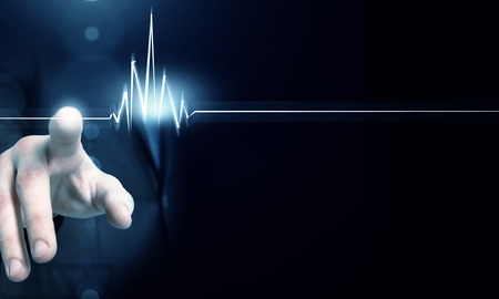 Male hand touch heart pulse on futuristic interface Stock Photo