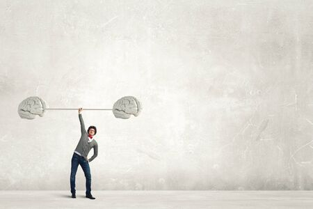 great idea: Confident businessman lifting above head barbell as symbol of great mind