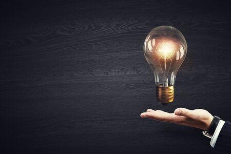 Cerca de la mano humana que sostiene el vidrio brillante bombilla
