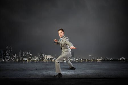 self defence: Cheerful young businessman demonstrating self defence element