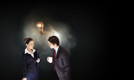 Partnership concept with businessman and businesswoman and glowing light bulb Stock Photo