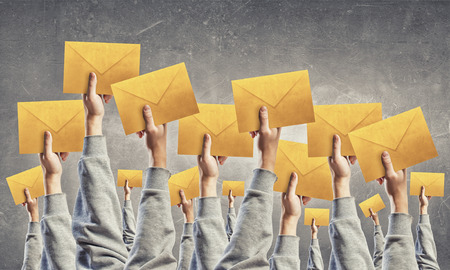 email: Crowd of businesspeople lifting up hands with email signs