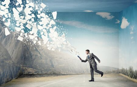 well read: Young businessman running with book in hand and pages flying in air