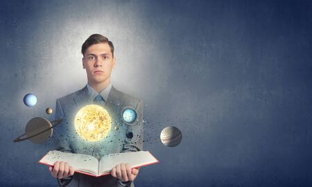 tell fortune: Young businessman with book and planets of space spinning around Stock Photo