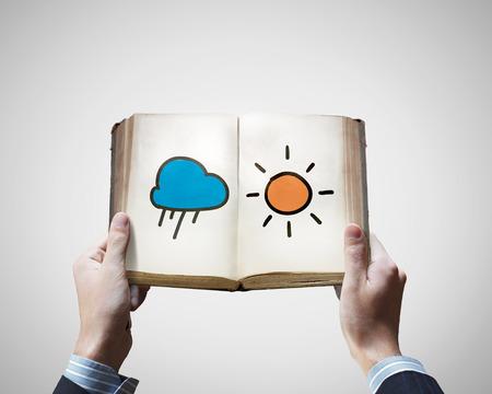 Cerca de las manos masculinas que sostiene el libro viejo con el sol una ilustración nube