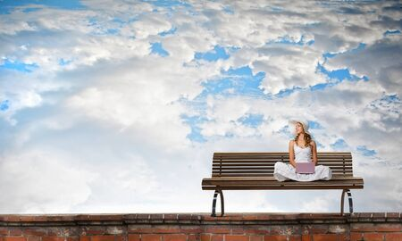 Young lady sitting on bench and using laptop Stock Photo