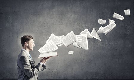 book pages: Young businessman with opened book in hands and pages flying in air Stock Photo