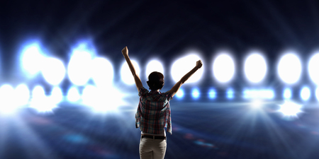 stage performer: Back view of girl with hands up standing in stage lights