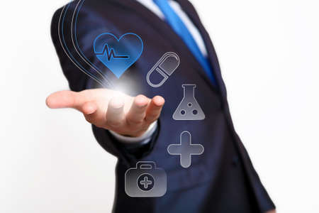 medical choice: Hand of businessman presenting icons on virtual screen Stock Photo