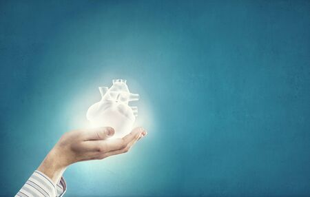 human hands: Close up of human hands holding human heart