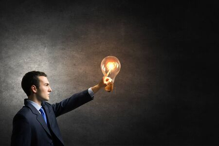 reaching hand: Businessman reaching hand to touch glass light bulb Stock Photo