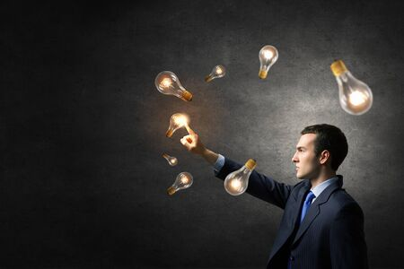 constructive: Businessman reaching hand to touch glass light bulb Stock Photo