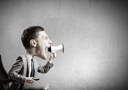emotional: Funny young man with big head screaming emotionally in megaphone Stock Photo