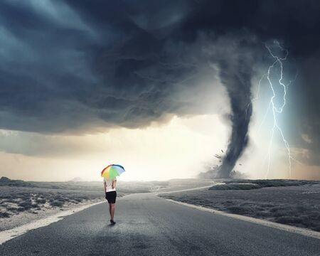 calm woman: Young pretty businesswoman with rainbow colorful umbrella walking in storm