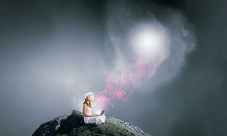 Young lady sitting on top of mountain with laptop Stock Photo