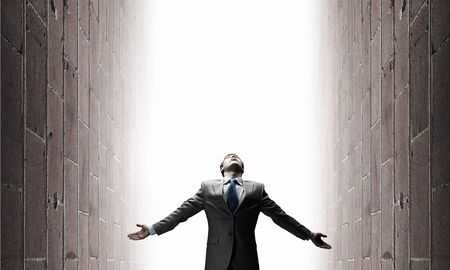 between: Businessman with hands spread apart standing in light coming from above Stock Photo