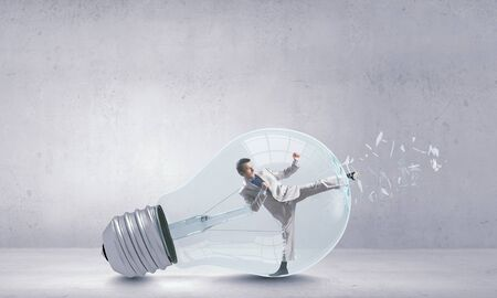 get out: Businessman inside light bulb braking it to get out