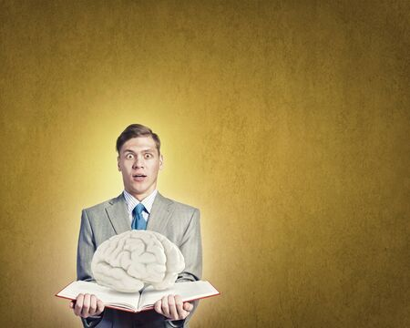 broaden: Shocked businessman holding opened book with brain picture Stock Photo