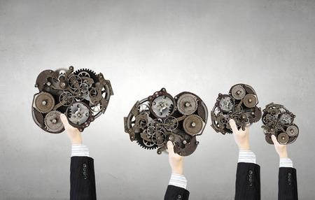 mechanisms: Hands of businesspeople holding gears engine mechanisms