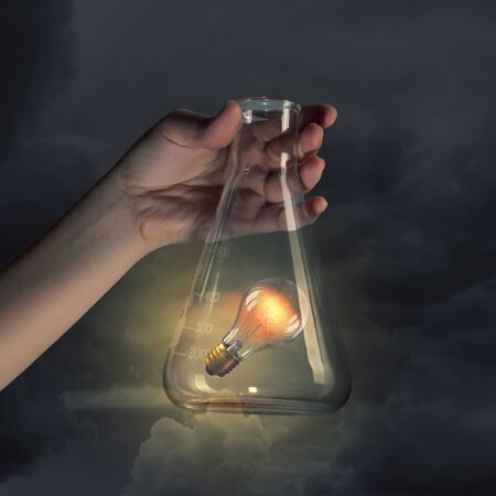 laboratorian: Hand holds flask with glass light bulb inside