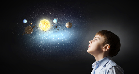 exploring: Cute boy of school age exploring space system Stock Photo