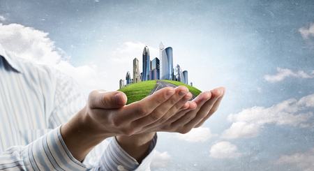 future city: Close up of hands holding image of modern cityscape
