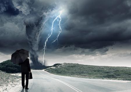 tornado: Back view of businessman with umbrella and suitcase facing tornado Stock Photo