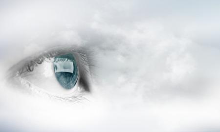 blue eye: Female blue eye on cloudy sky background
