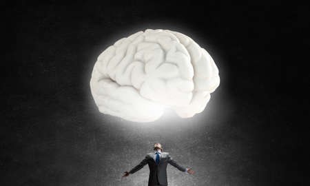 human hands: Businessman with hands spread wide and human brain above his head Stock Photo