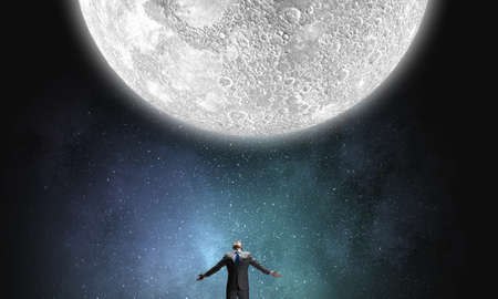moon gate: Businessman with hands spread apart looking at moon above Stock Photo