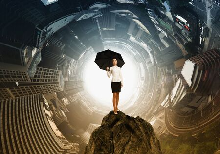 pessimist: Young businesswoman with black umbrella standing on top Stock Photo