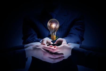 개념: 다양한 비즈니스 사람들이 손에 전구를 들고와 브레인 스토밍과 팀워크 개념