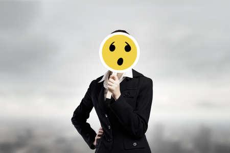 hidden success: Unrecognizable businesswoman hiding her face behind mask