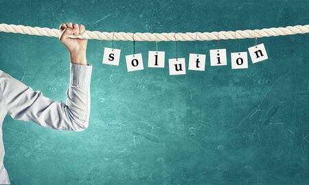 Word solution composed of cards hanging on rope Stock Photo