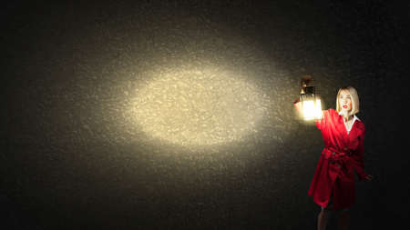 cloak: Young blond woman in red cloak with lantern lost in darkness