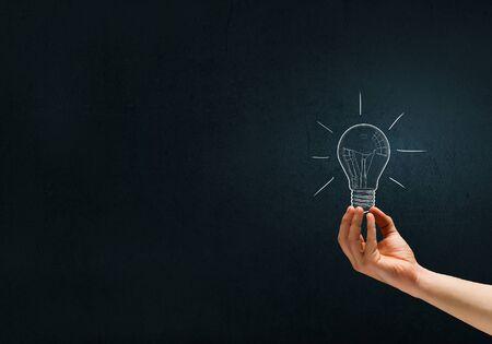 artifical: Human hand on dark background holding light bulb