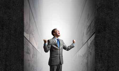 emotionally: Young confident businessman with hands up screaming emotionally above Stock Photo