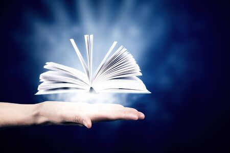book concept: Close up of hand holding in palm glowing book