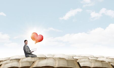 heart intelligence: Young emotional businessman with opened book in hand