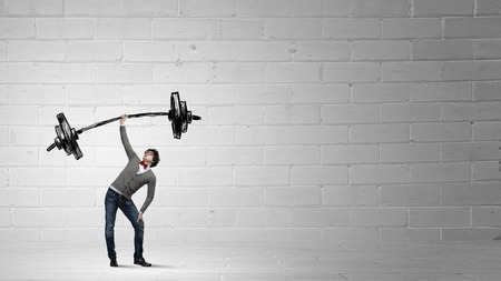 above head: Confident businessman lifting above head barbell with light bulbs Stock Photo