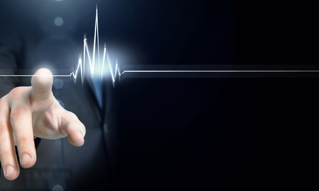 heartbeat line: Male hand touch heart pulse on futuristic interface Stock Photo