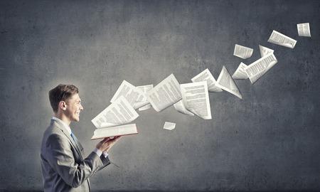 Junge Unternehmer mit geöffnetem Buch in den Händen und Seiten fliegen in der Luft Standard-Bild
