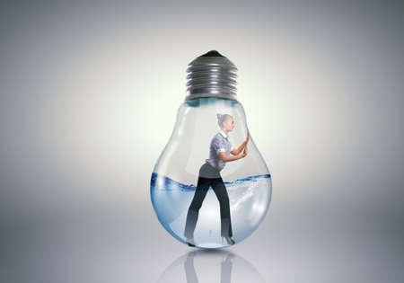 female prisoner: Businesswoman inside light bulb trying to get out Stock Photo
