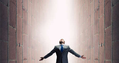 light to dark: Businessman with hands spread apart standing in light coming from above Stock Photo
