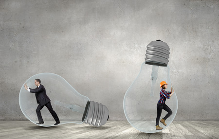 get out: Businesswoman and businessman inside light bulb trying to get out Stock Photo