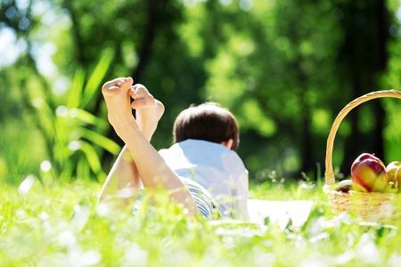 Kind liegt auf Decke mit Picknick im Sommer Park